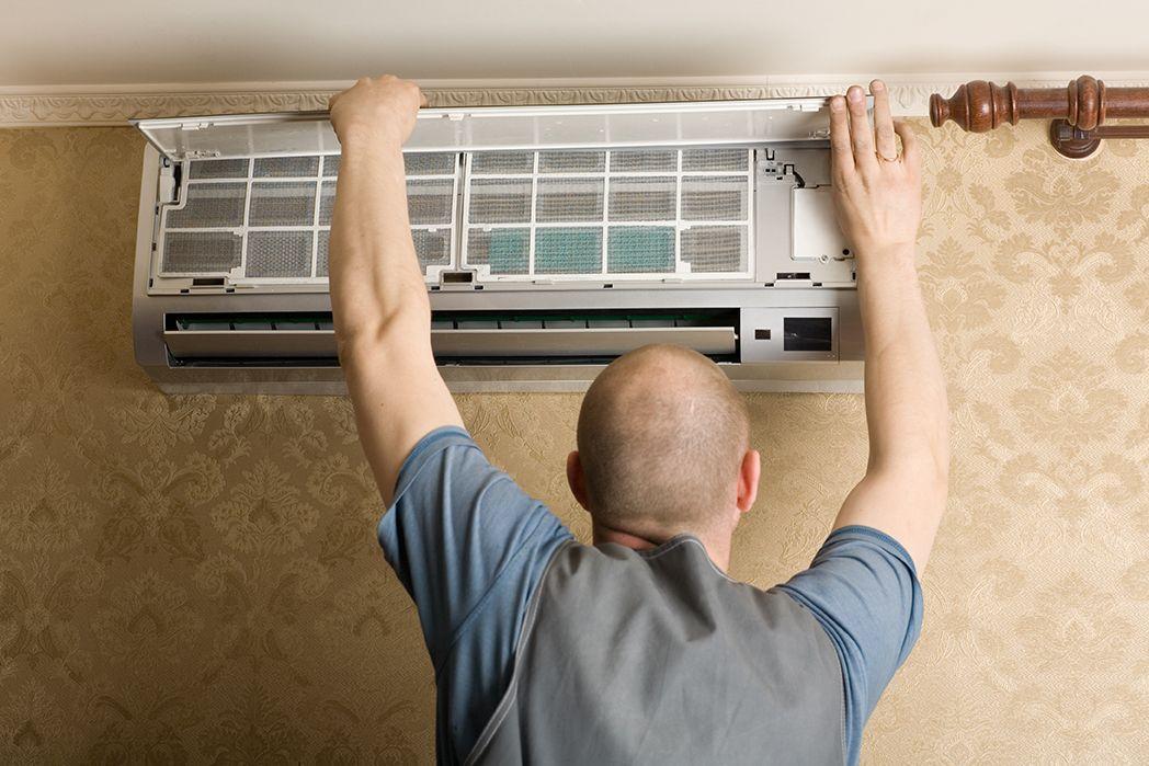 Man Performing HVAC Repair in Boca Raton on wall AC unit